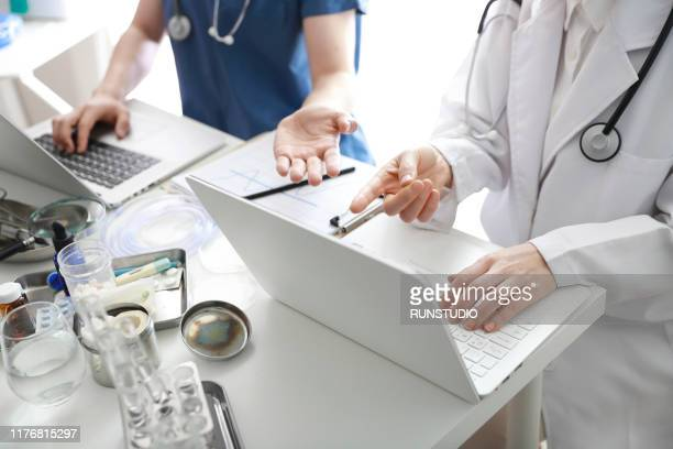 doctors using laptop in meeting - データ  ストックフォトと画像