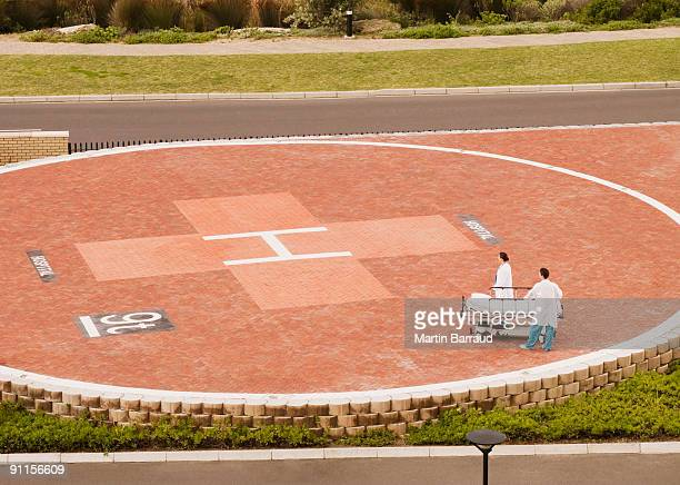 doctors waiting for helicopter with gurney - helipad stock photos and pictures