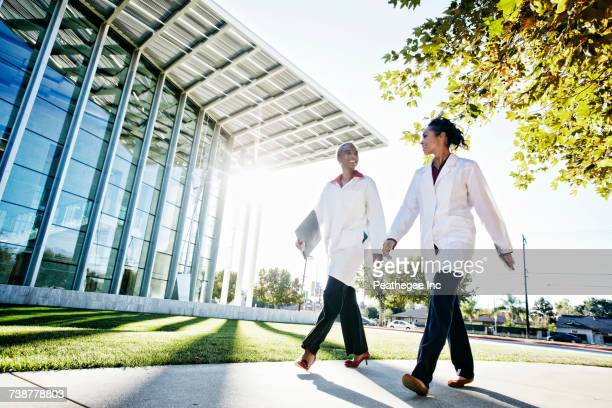 Doctors walking and talking outdoors at hospital