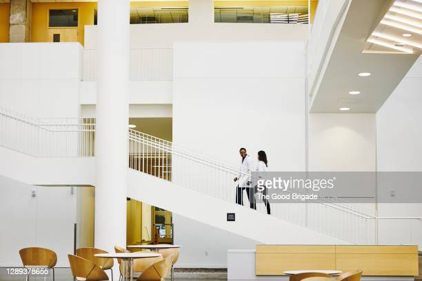 doctors walking up staircase in hospital lobby - hospital stock pictures, royalty-free photos & images