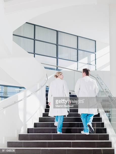 doctors walking up staircase in hospital - medical building stock pictures, royalty-free photos & images
