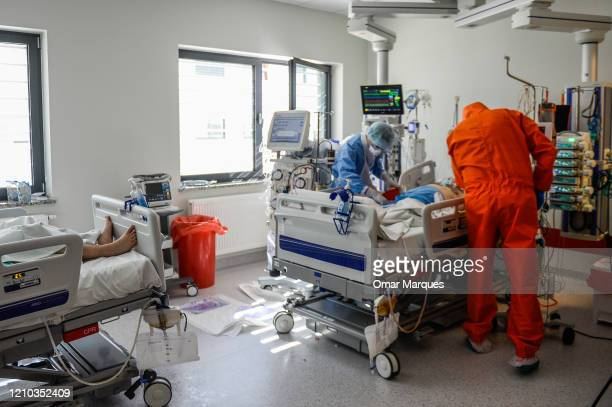 Doctors wear protective, suits, masks, goggles and gloves as they perform a medical procedure in the femoral artery of a COVID - 19 patient inside...
