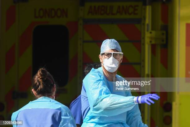 Doctors wearing protective equipment are seen loading a patient in to an ambulance outside St Thomas' Hospital on April 7, 2020 in London, England....