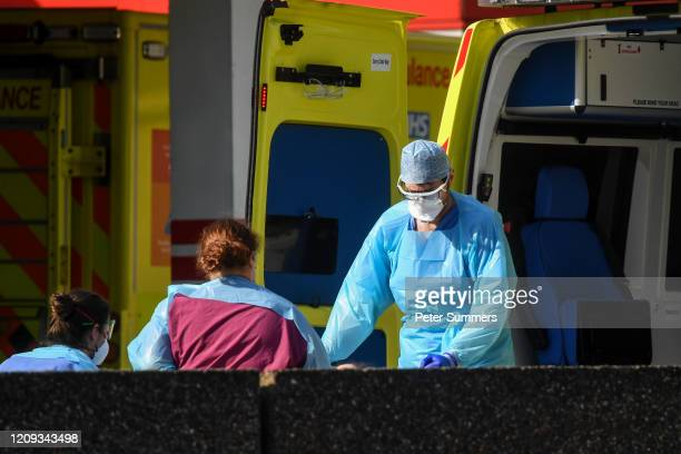 Doctors wearing protective equipment are seen loading a patient in to an ambulance outside St Thomas' Hospital on April 7 2020 in London England...