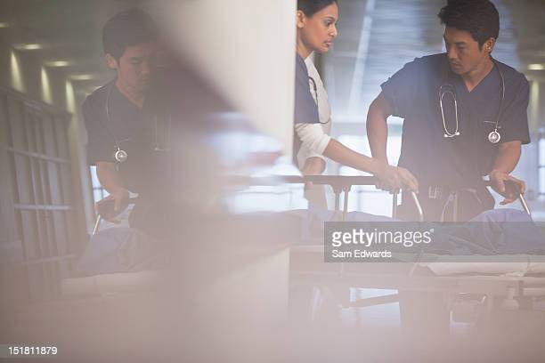 Doctors wheeling patient on gurney in hospital corridor