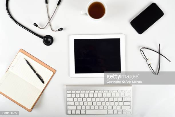 Doctors White office desk table with tablet and smartphone. Top view with blank screen and copy space
