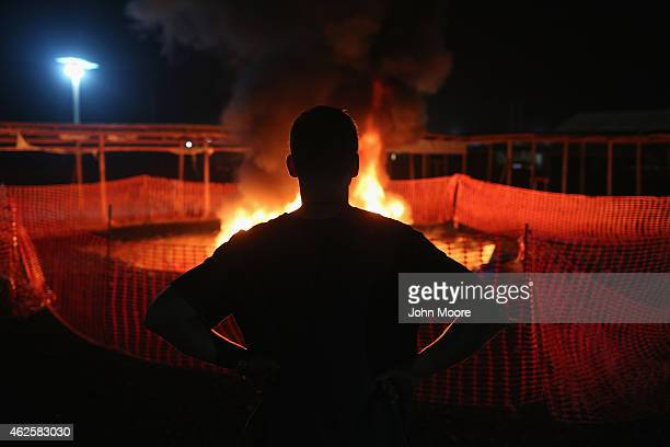Doctors Without Borders staffer Alex Eilert Paulsen watches as mattresses and bed frames burn at the Ebola Treatment Unit on January 31 2015 in...