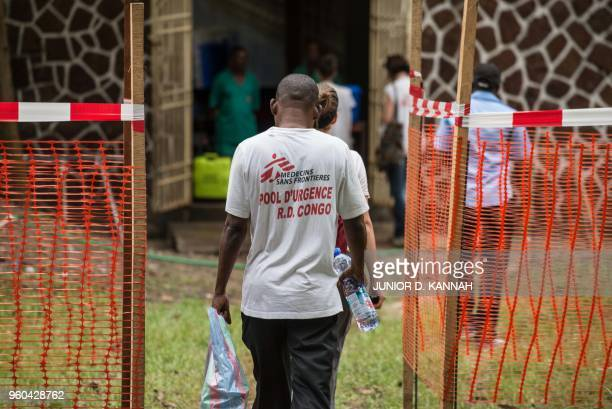 TOPSHOT Doctors Without Borders team members walk through an Ebola security zone at the entrance of the Wangata Reference Hospital in Mbandaka...