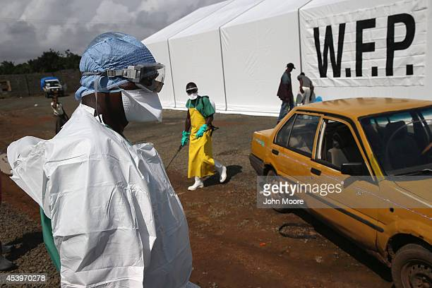A Doctors Without Borders worker in protective clothing stands by as people arrive requesting to be tested for the Ebola virus at the MSF treatment...