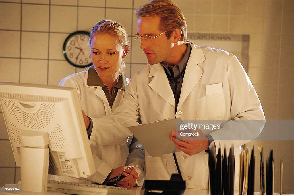 Doctors working together on computer : Stockfoto