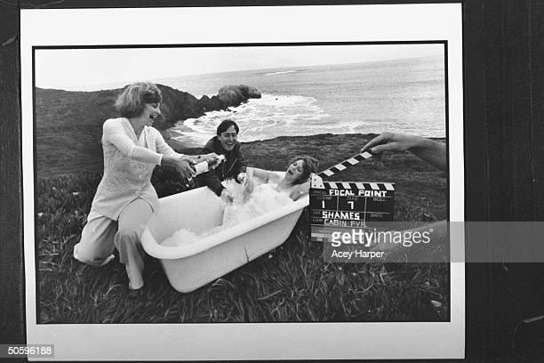 Documentary filmmaker Deborah Shames spoofing herself as dir of her soft porn video Cabin Fever while sitting on edge of bathtub pouring champagne...