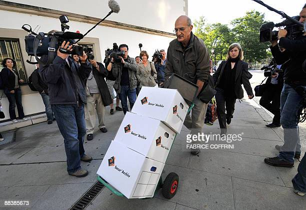 Documents are carried to the courthouse on June 10 2009 on the opening day of Cecile Brossard's trial in Geneva Banker Edouard Stern one of France's...