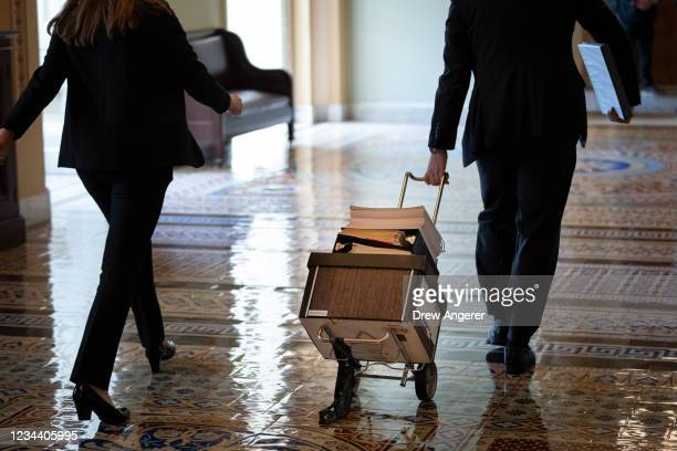 Documents, including text of the bipartisan infrastructure legislation, is wheeled toward the office of Senate Majority Leader Chuck Schumer at the...