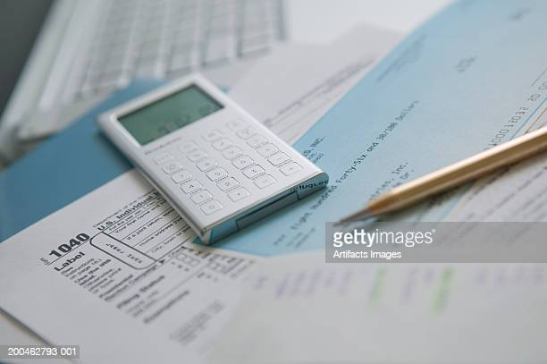 documents with calculator and pen - 1040 tax form stock photos and pictures