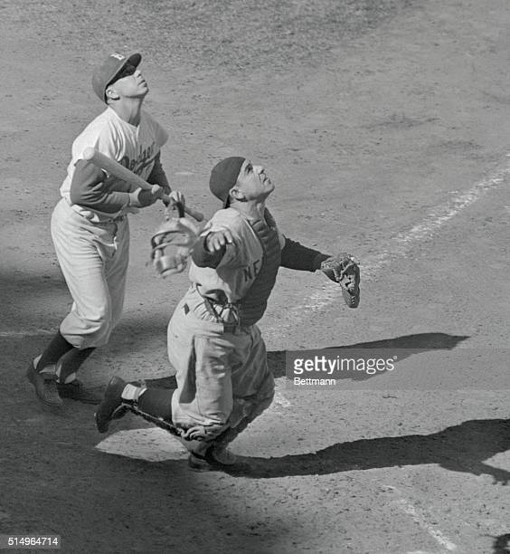 Dodger captain PeeWee Reese watches helplessly as Yankee catcher Yogi Berra prepares to catch his popup for out number one in the sixth inning of the...