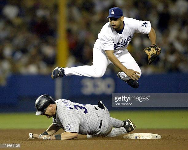 Dodgers Alex Cora goes up and over Rockies Larry Walker to turn the double play in the 7th inning Los Angeles Dogers win the first of a 3 games series