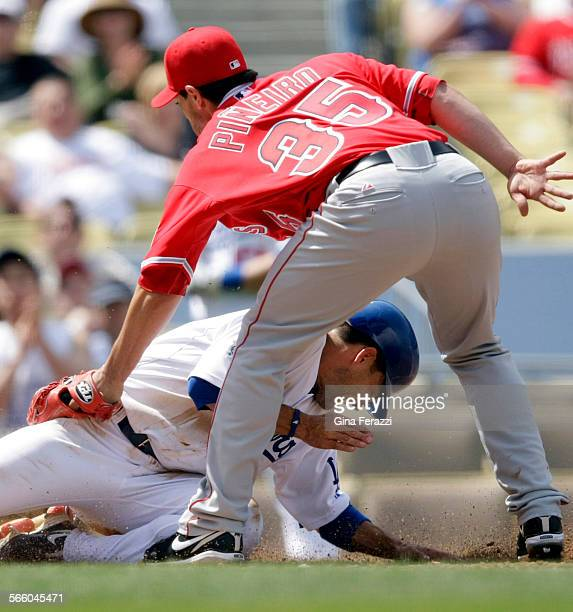 Dodgers Jamey Carroll slides safely into home after Angels pitcher Joel Pineiro threw a wild pitch in the second inning at Dodger Stadium