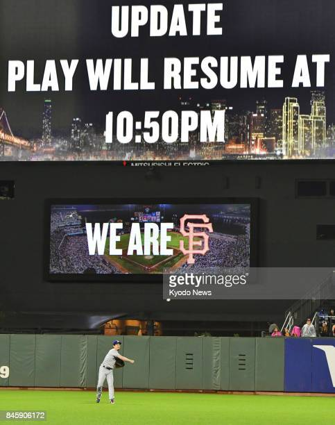 Dodgers pitcher Kenta Maeda is seen warming up in front of a big screen that notifies fans when the game between the San Francisco Giants and the Los...