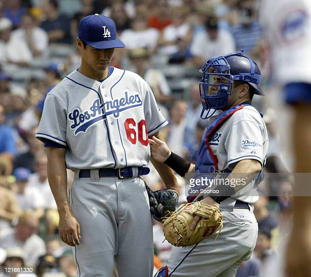 Dodgers' pitcher Masao Kida and catcher Paul Loduca talk in the first inning at Wrigley Field