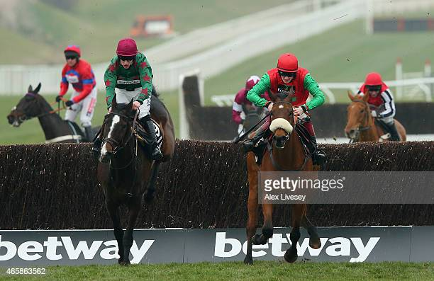 Dodging Bullets ridden by Sam TwistonDavies clears the last fence ahead of Somersby ridden by Brian Hughes to win the Betway Queen Mother Champion...