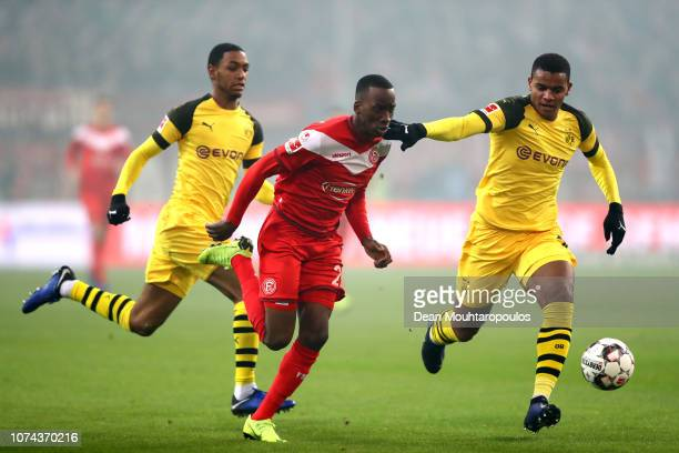 Dodi Lukebakio of Fortuna Duesseldorf runs with the ball under pressure from Abdou Diallo of Borussia Dortmund and Manuel Akanji of Borussia Dortmund...