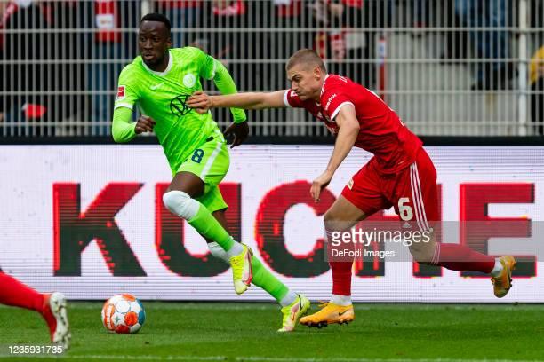 Dodi Lukebakio of VfL Wolfsburg and Julian Ryerson of 1. FC Union Berlin battle for the ball during the Bundesliga match between 1. FC Union Berlin...