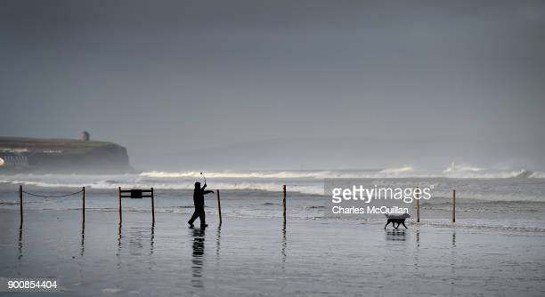 A dog and his owner enjoy a break in the weather after Storm Eleanor recorded winds of up to 90mph on January 3 2018 in Portrush Northern Ireland The...
