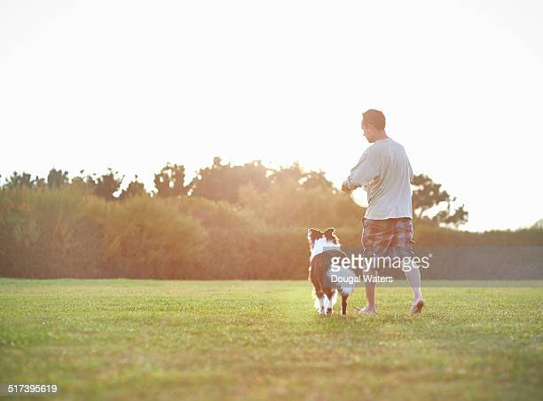 Dog and owner in field with frisbee.