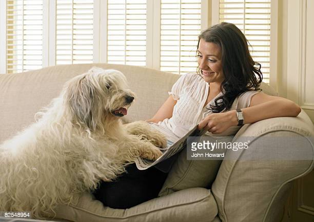 Dog and owner lying on sofa