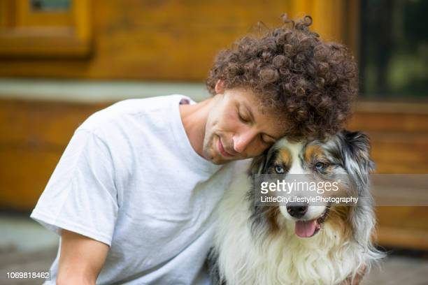 dog and owner relaxing - pastore australiano foto e immagini stock