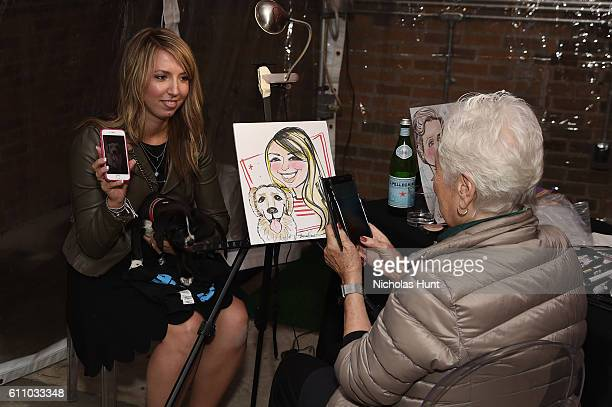 Dog and their owner participate in a caricature drawing during the celebration of the launch of Rachael Ray's Nutrish DISH with a Puppy Party on...