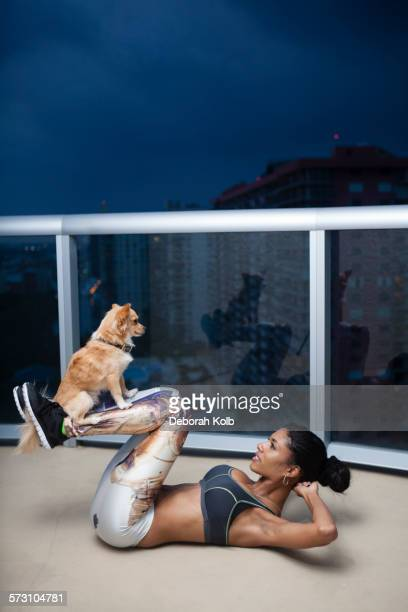 Dog balancing on legs of mixed race athlete during exercise