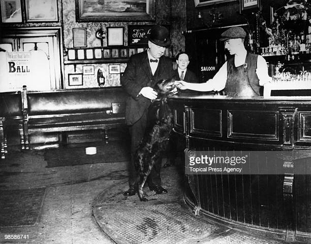 A dog delivers a pay envelope to a bartender in New Cross Gate London December 1922