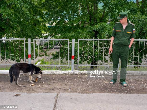 A dog feeds next to a soldier at a station on the route of the TransSiberian Railway from MoscowVladivostok Spanning a length of 9289km it's the...