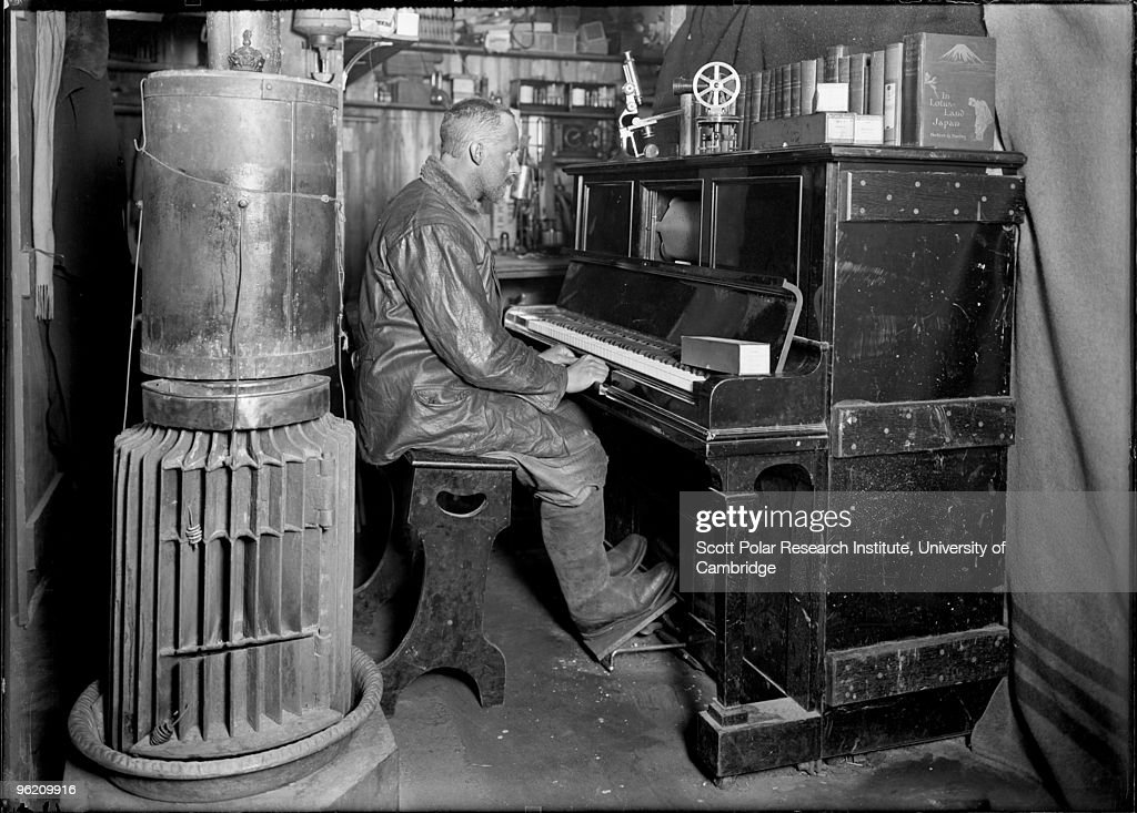 Dog handler Cecil Meares (1877 - 1937) at the pianola in the Winterquarters hut, in the Ross Dependency of Antarctica, during Captain Robert Falcon Scott's Terra Nova Expedition to the Antarctic, January 1912.