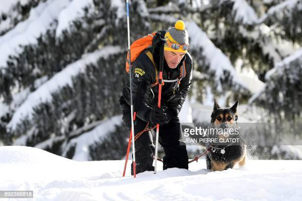 A dog handler rescuer takes part in a mock rescue operation during an avalanche exercice on December 19 2017 in Les Gets / AFP PHOTO / JEANPIERRE...