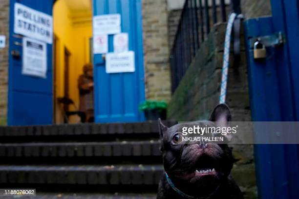 A dog is tied up to railings outside St John's parish hall polling station in London as Britain holds a general election on December 12 2019