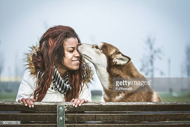 Dog kissing a young woman