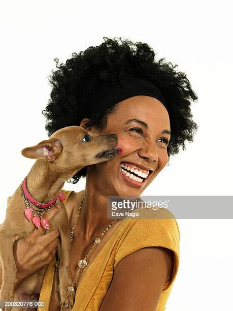 Dog kissing young woman, close-up