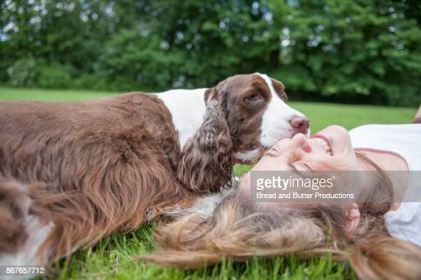 Dog Licking Smiling Woman who is Lying on her back on the Grass Outdoors