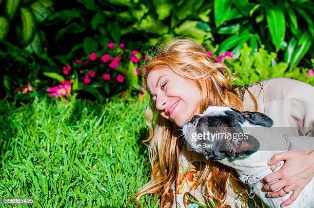 Dog licking womans face in garden