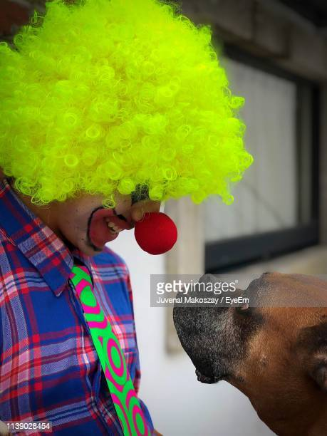 Dog Looking At Man Dressed As Clown