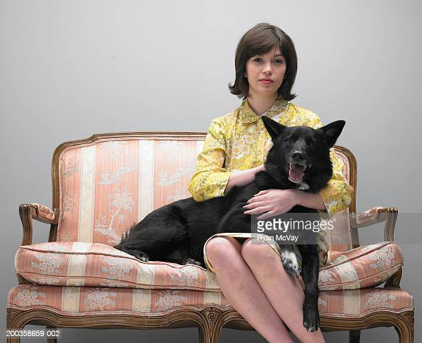 Dog lying across young woman's lap on love seat, portrait