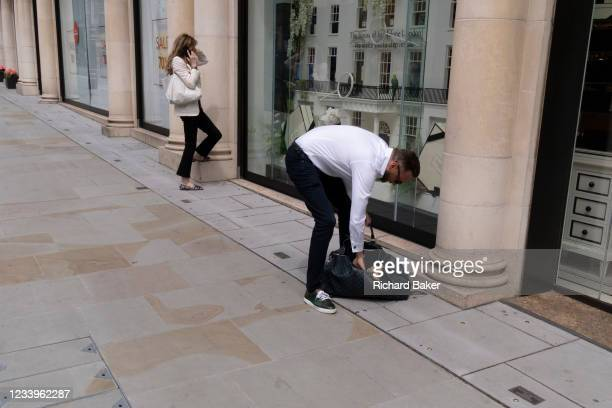 Dog owner folds his spaniel into a shoulder bag for safety on New Bond Street, on 12th July 2021, in London, England.