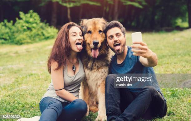 Dog owners taking selfie with dog in the city park