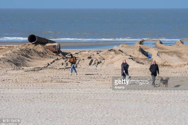 Dog owners walking their dogs on beach during sand replenishment / beach nourishment project to make wider beaches at the Belgian coastline