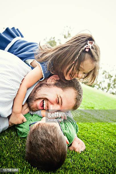 dog pile on top of daddy - rough housing stock photos and pictures