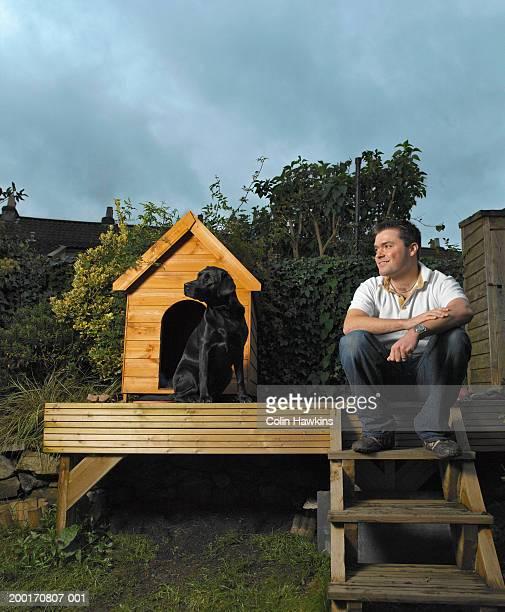 Dog sitting outside kennel in garden, man sitting on steps nearby