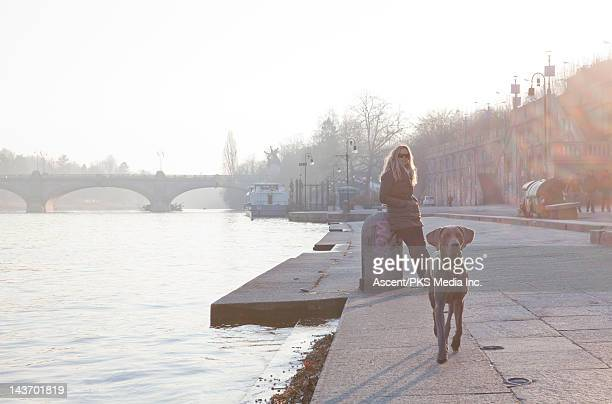 Dog stands guard for a woman on a riverside walk