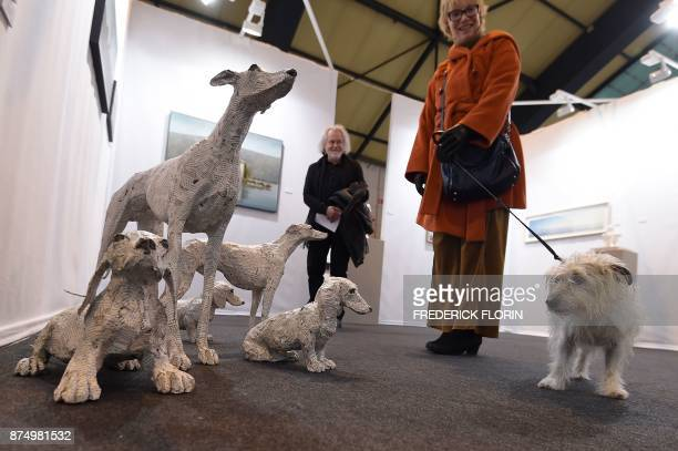 A dog stands next to sculptures by Italian artist Claudio Locatelli during a private preview of the 'START' European contemporary art fair on...